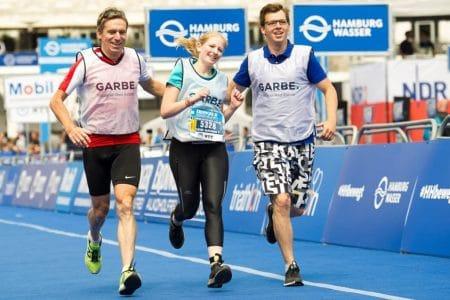 Eine Frau und zwei Männer laufen bei einem Marathon