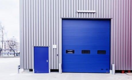Blaue Eingangstür und blaue Beladetür